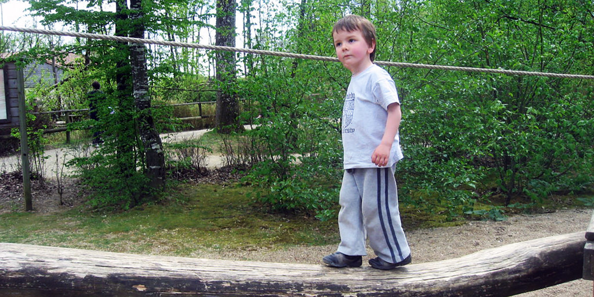 Boy balancing on a log